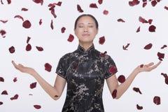 Vrouw in traditionele kleding en wapens uitgestrekt met roze bloemblaadjes die onderaan rond haar in medio lucht, studioschot kome Royalty-vrije Stock Afbeelding