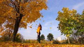 Vrouw trow omhoog in bladeren van de lucht de gele esdoorn De heldere kleurrijke zonnige herfst stock footage