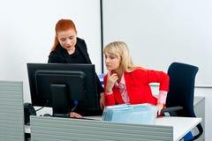 Vrouw twee die colegues aan computer in bureau werken Stock Foto's