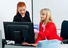 Vrouw twee die colegues aan computer in bureau werken Stock Afbeeldingen