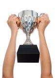 Vrouw twee hand die een kampioens zilveren trofee op witte backgro houden Royalty-vrije Stock Foto's