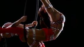 Vrouw twee in maakt element in de luchthoepel Zwarte achtergrond Langzame Motie Sluit omhoog stock video