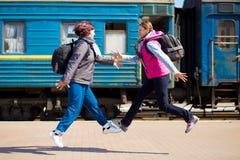 Vrouw twee met rugzak bij station in werking dat wordt gesteld dat stock foto