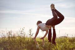 Vrouw twee op gebied die de oefening van de geschiktheidsyoga samen doen stock afbeeldingen