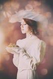 Vrouw in uitstekende kleding met plaathoogtepunt van chocolade Royalty-vrije Stock Foto