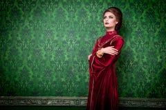 Vrouw in uitstekende kleren op rococo'smuur stock foto's