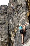 Vrouw van de bergbeklimmings hangt de mannelijke instructeur kabel Stock Afbeeldingen