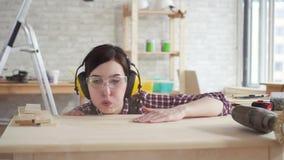 Vrouw van de close-up blaast de jonge professionele timmerman schaafsel van de lijst, langzame mo stock videobeelden