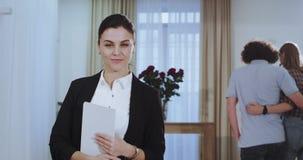 Vrouw van de portret beëindigt de aantrekkelijke makelaar in onroerend goed de vergadering met haar cliënt terwijl jong koppelt g stock footage