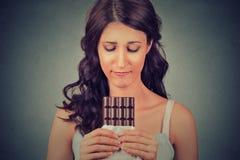 Vrouw van dieetbeperkingen wordt vermoeid die snoepjes naar chocolade hunkeren die Stock Foto