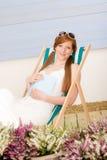 Vrouw van het het terras ontspant de rode haar van de zomer in deckchair Stock Foto's