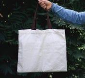 vrouw van het katoen Tote Bag van de handholding op groene bladachtergrond stock foto