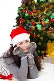 Vrouw in van het Kerstmanhoed en bont vuisthandschoenen die onder Kerstboom liggen Stock Foto's