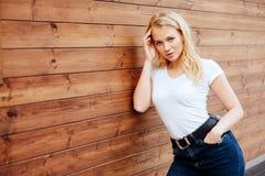 Vrouw van het manier de jonge blonde over houten achtergrond stock fotografie