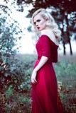 Vrouw van het manier de schitterende jonge blonde in mooie rode kleding in een sprookje bos magische atmosfeer Retoucheerd stemme Royalty-vrije Stock Fotografie