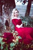 Vrouw van het manier de schitterende jonge blonde in mooie rode kleding in een sprookje bos magische atmosfeer Retoucheerd stemme Stock Fotografie