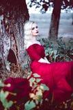 Vrouw van het manier de schitterende jonge blonde in mooie rode kleding in een sprookje bos magische atmosfeer Retoucheerd stemme Stock Afbeelding