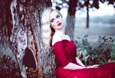 Vrouw van het manier de schitterende jonge blonde in mooie rode kleding in een sprookje bos magische atmosfeer Retoucheerd stemme Stock Afbeeldingen