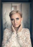 Vrouw van het schoonheids de verse blonde met mooie blauwe ogen in het witte bruids kleding stellen stock foto