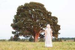 Vrouw voor de grote boom in de park uitstekende stijl in groene aarde van de concepten de eenzame, alleen aard Stock Foto