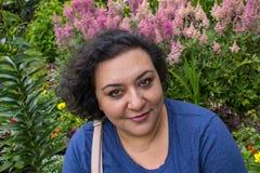 vrouw voor roze bloemen stock foto