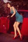Vrouw vooraan rode auto Royalty-vrije Stock Foto's