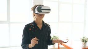 Vrouw in VR-hoofdtelefoon die omhooggaand en voorwerpen in virtuele werkelijkheid proberen thuis binnen te raken kijken stock video