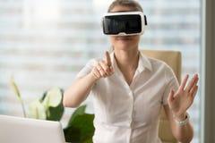 Vrouw in VR-hoofdtelefoon wat betreft virtuele voorwerpen Stock Fotografie