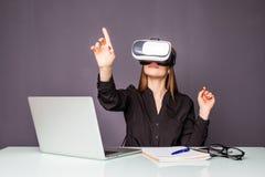 Vrouw in VR-hoofdtelefoon wat betreft voorwerpen in virtuele werkelijkheid Meisjeszitting in leunstoel bij het bureau en het in w Royalty-vrije Stock Afbeelding
