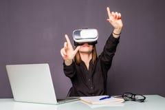 Vrouw in VR-hoofdtelefoon wat betreft voorwerpen in virtuele werkelijkheid Meisjeszitting in leunstoel bij het bureau en het in w Royalty-vrije Stock Foto's