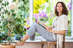 Vrouw vrij op middelbare leeftijd met een boek dichtbij een open venster stock afbeeldingen