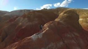 Vrouw wandeling die naar de rode bergpiek stijgen stock footage