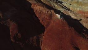 Vrouw wandeling die naar de rode bergpiek stijgen stock videobeelden