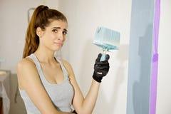 Vrouw wanhopig en over het schilderen van huis wordt vermoeid dat stock afbeelding