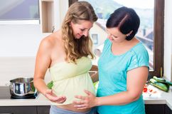 Vrouw wat betreft babybuik van beste vriend Royalty-vrije Stock Foto