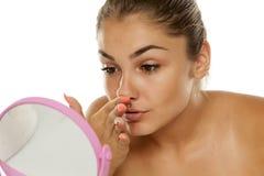 Vrouw wat betreft haar neus stock fotografie