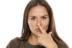 Vrouw wat betreft haar neus stock afbeeldingen