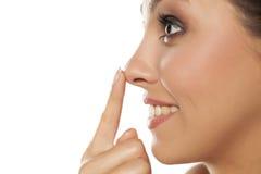 Vrouw wat betreft haar neus stock afbeelding