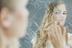 Vrouw wat betreft haar spiegelgedachtengang royalty-vrije stock afbeeldingen