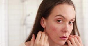 Vrouw wat betreft huid in ongelukkige badkamers stock video