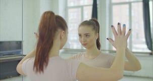 Vrouw wat betreft spiegel terwijl het bekijken bezinning stock videobeelden
