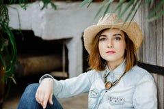 Vrouw in westelijke slijtage in cowboyhoed, jeans en cowboylaarzen stock afbeeldingen
