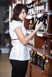 Vrouw in wijnwinkel Stock Foto