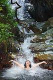 Vrouw in wilde waterval Stock Foto