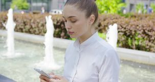 Vrouw in wit overhemd die telefoon met behulp van stock video