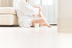Vrouw in witte badjaszitting op vloer. Royalty-vrije Stock Fotografie