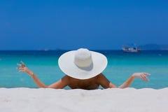 Vrouw in witte hoed die op het strand liggen stock afbeeldingen