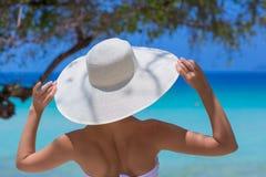 Vrouw in witte hoed die zich op het strand bevinden stock fotografie