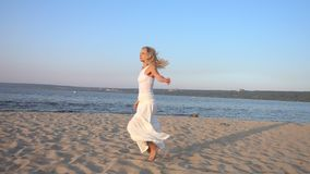 Vrouw in witte kleding die op het strand dansen stock footage