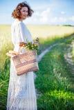 Vrouw in witte kleding met mand met brood en melk het lopen alo Stock Afbeeldingen